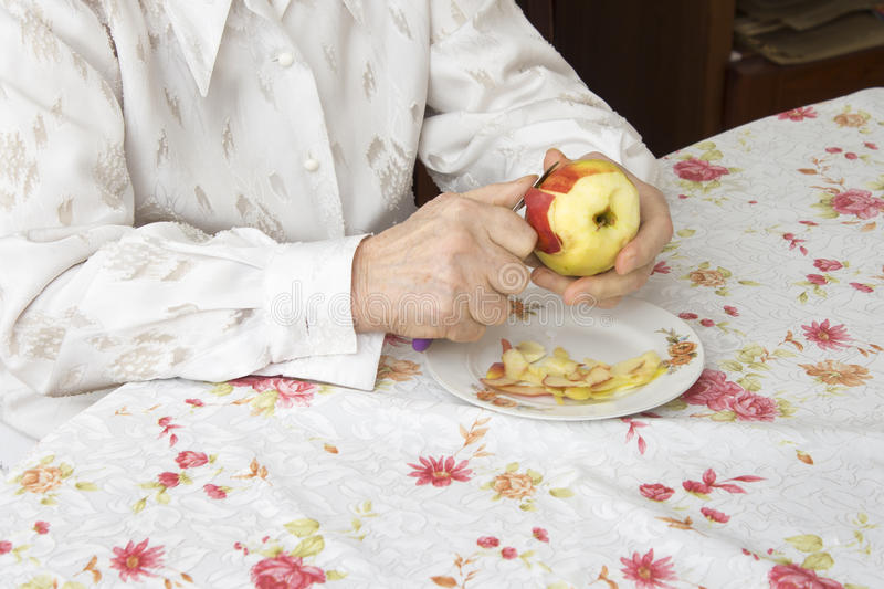 Hands of the old woman peeling an apple. royalty free stock photography