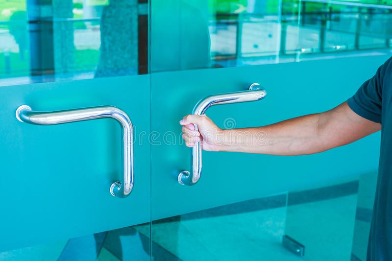 Man hands open the blue glass door. Hands open the blue glass door royalty free stock image