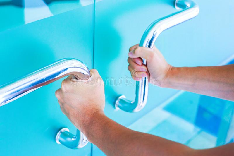 Hands open the blue glass door. Man hands open the blue glass door stock photos