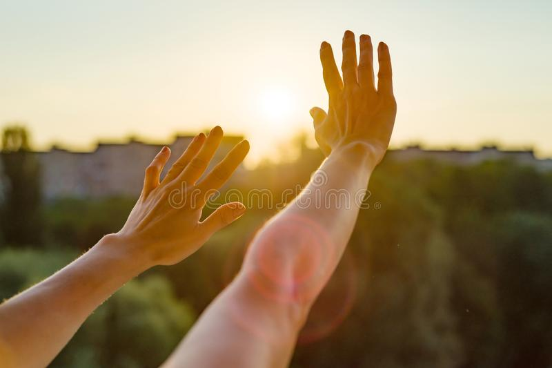 Hands open to the sunset, meditation, religion, prayer, background of the open window in the house, the silhouette of the city and stock photos