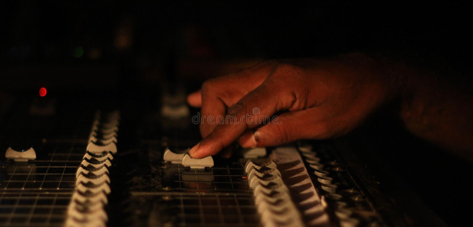 Hands operating slider of light and sound board console at a concert theater.  stock image