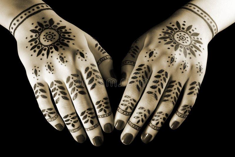 Hands with oriental tattoo. Nice closeup women's hands with oriental tattoo isolated over black royalty free stock photo