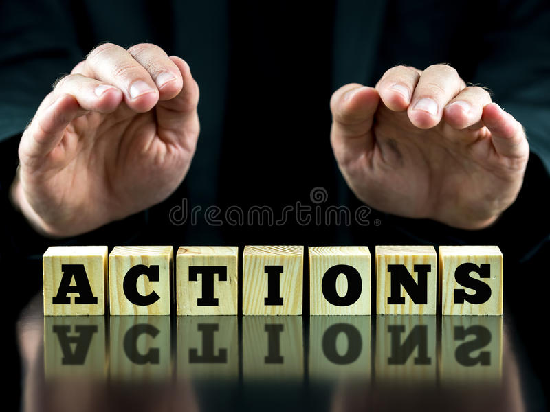 Hands Over Letter Tiles Spelling the Word Actions. Hands Hovering Over Letter Tiles Spelling the Word Actions with Reflection in Shiny Surface royalty free stock photography