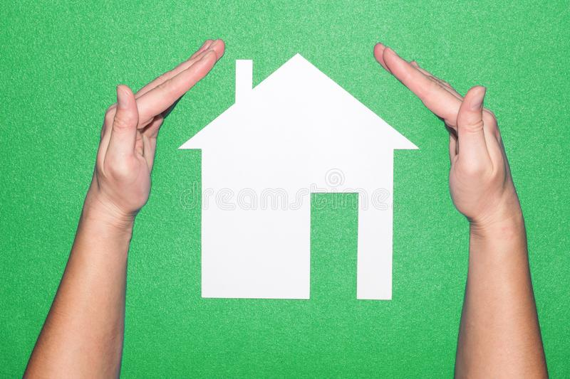 Hands over white paper house on a green background. protect the house. Home and Family Insurance. royalty free stock photography