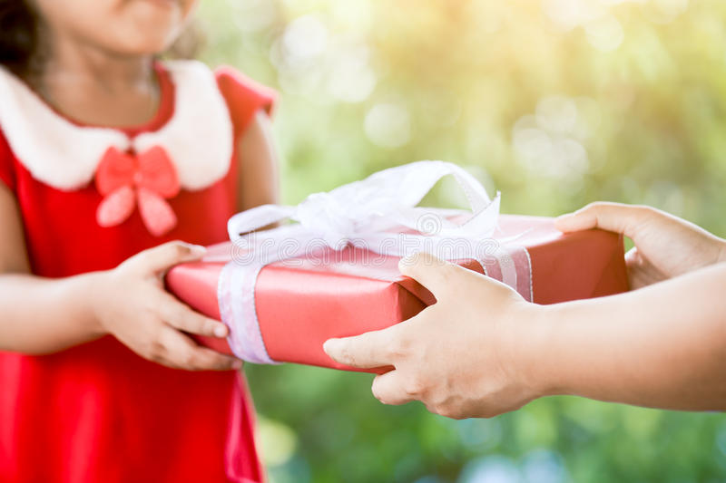 Hands of parent giving Christmas gift to child girl stock photo