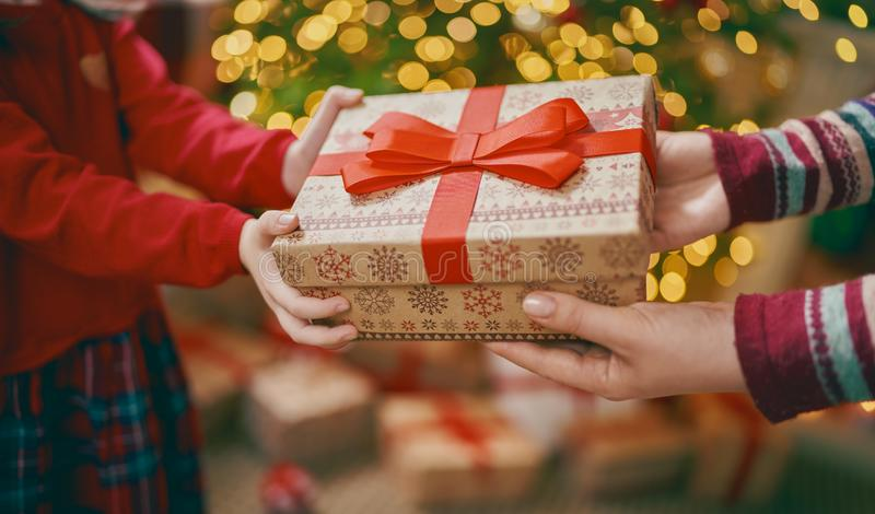 Hands of parent giving a x-mas gift to child stock image