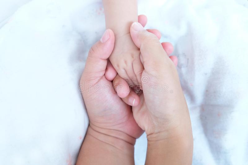 Hands of parent holding baby hand royalty free stock images