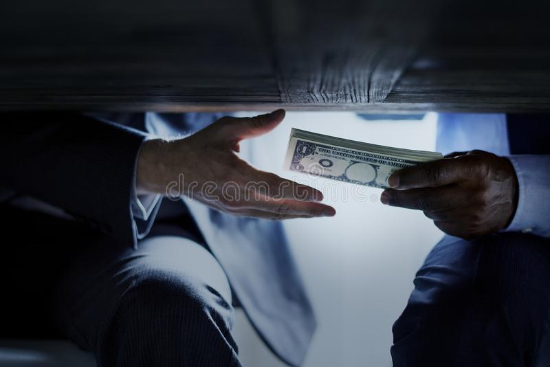 Hands passing money under table corruption bribery royalty free stock photos