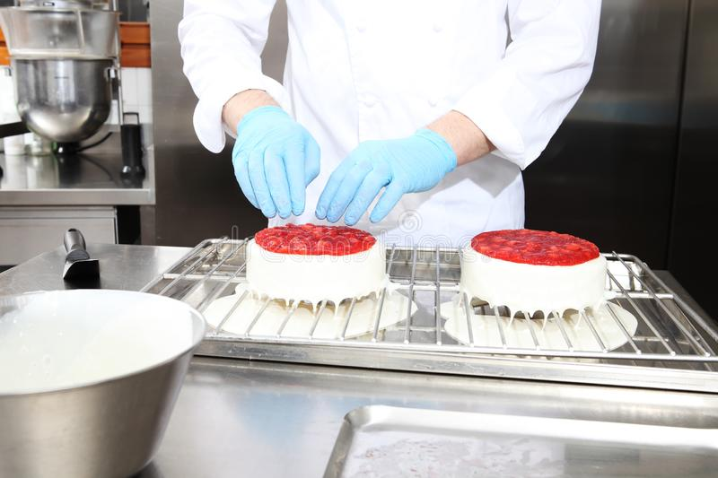 Hands pastry chef prepares a cake, cover with icing and decorate with strawberries, works on a stainless steel industrial kitchen stock photo