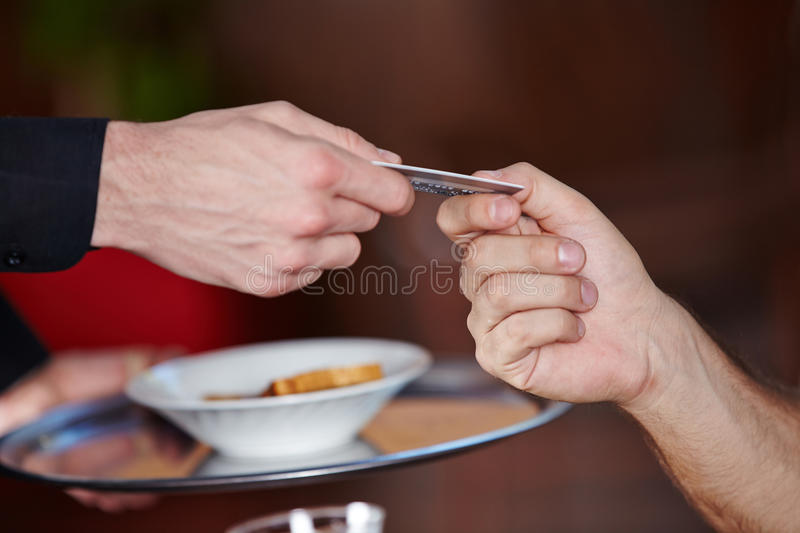 Hands paying with credit card. Hands in a restaurant paying with credit card royalty free stock image
