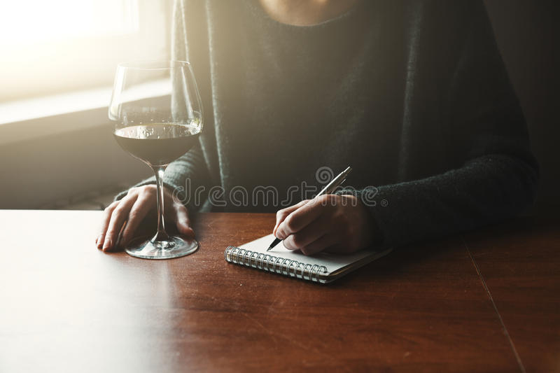 Hands with pen and glass of wine writing. Female hands with pen and glass of wine writing on notebook royalty free stock images