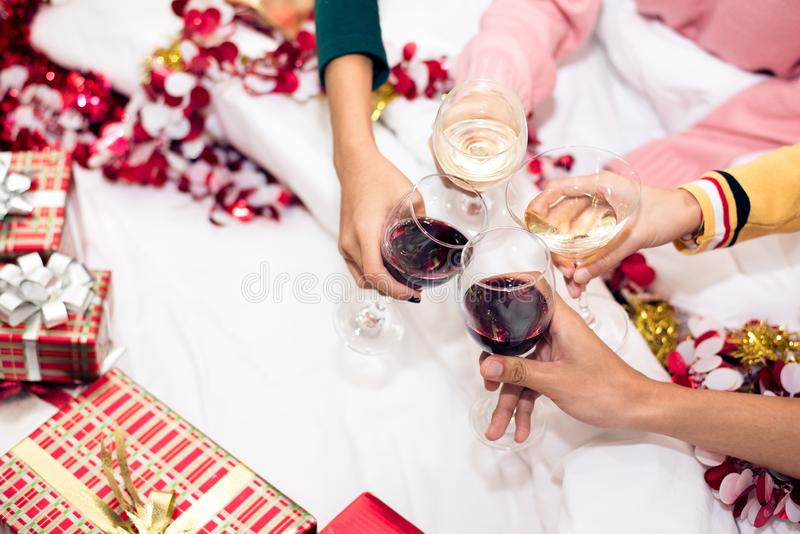 Hands of people celebrating New year party in home with wine drinking glasses. New year and Christmas party concept. Happiness royalty free stock photo
