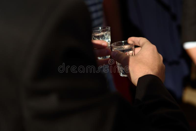 Hands of people clinking and toasting with glasses of vodka at w royalty free stock images