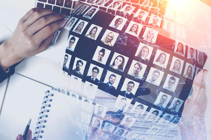 Hands of people in office, social media. Top view of business people hands working at office table with double exposure of diverse people portraits. Concept of royalty free stock images