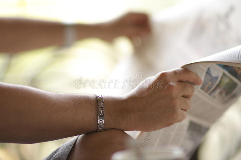 Hands of person with newspaper stock photography