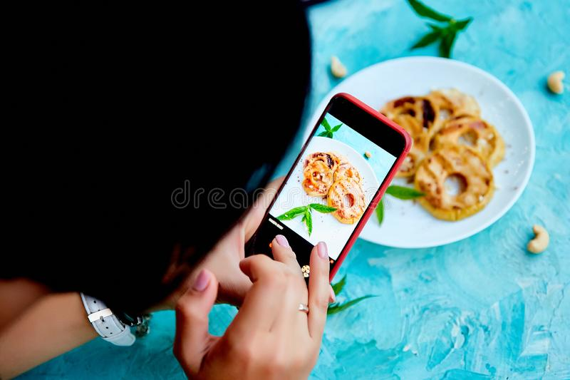 Food blogger using smartphone taking photo. Blogger girl royalty free stock photography