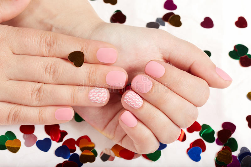 Hands with pink matte manicured nails. Hands with short pink matte manicured nails royalty free stock image