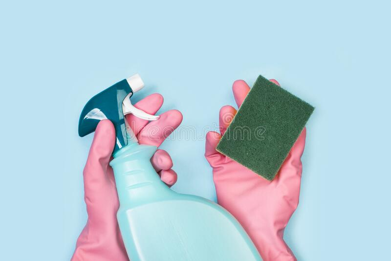 Hands with pink rubber gloves holding a cleaning sponge and a cleaning product sprayer. On a light blue background royalty free stock photo