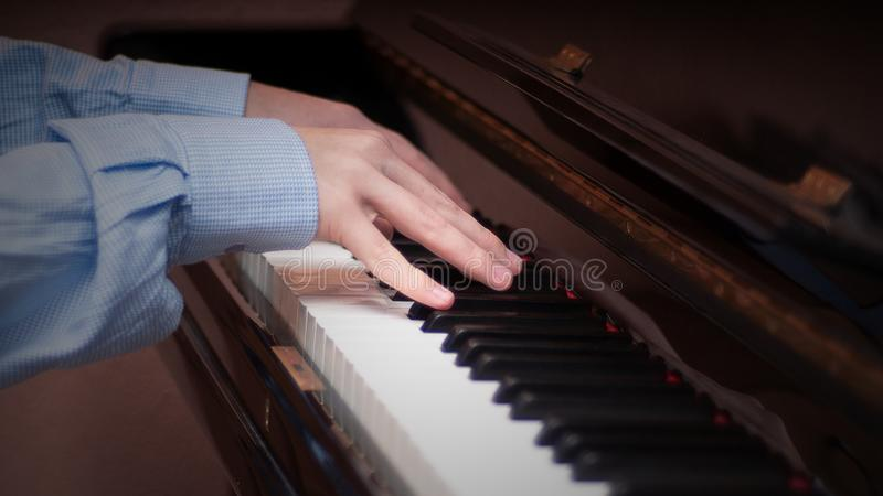 Hands playing on a piano royalty free stock image