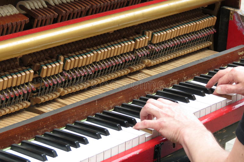 Hands playing upright piano stock photos