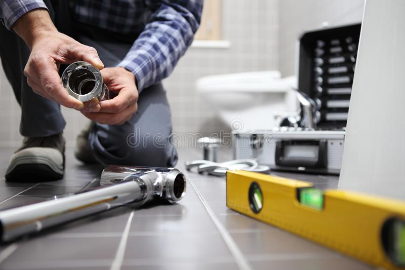 Hands plumber at work in a bathroom, plumbing repair service, as. Semble and install concept stock photo