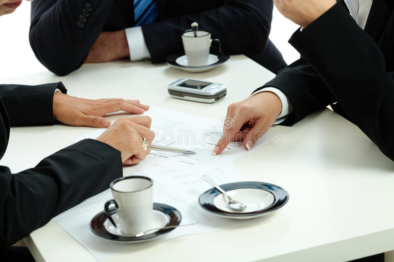 Hands pointing business chart. During business meeting on coffee table stock photo