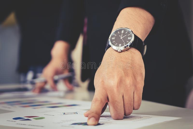 Hands pointing on data chart sheet in business meeting royalty free stock photography