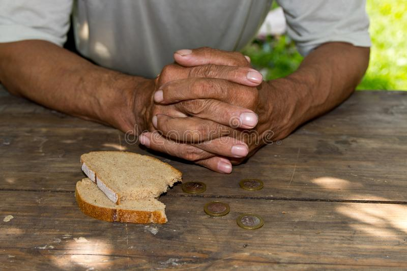 Hands the poor old man`s, piece of bread and change, pennies on wood background. The concept of hunger or poverty. stock photo
