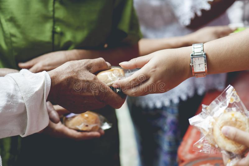 Hands of the poor receive food from the donor`s share. poverty concept.  stock photos