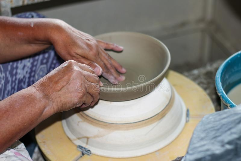 Hands of a potter, creating an bowl on the circle. Pottery polishing process with 2 hands in the final step. Before entering the kiln stock photos