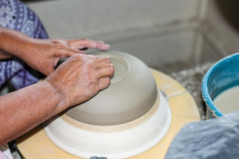 Hands of a potter, creating an bowl on the circle. Pottery polishing process with 2 hands in the final step. Before entering the kiln royalty free stock photography