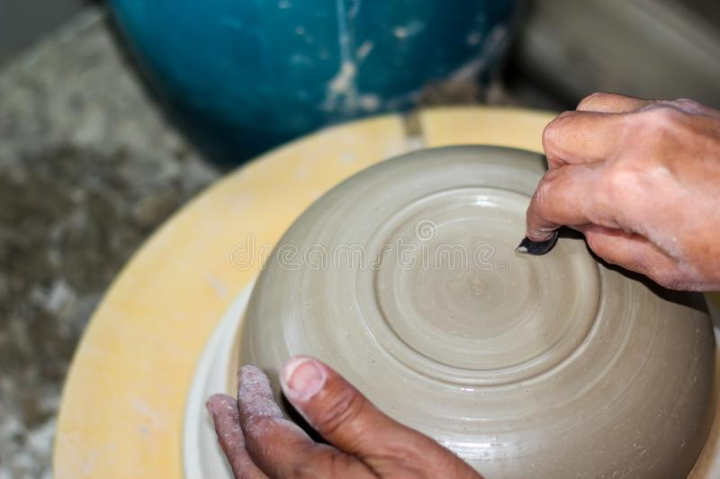 Hands of a potter, creating an bowl on the circle. Pottery polishing process with 2 hands in the final step. Before entering the kiln royalty free stock images