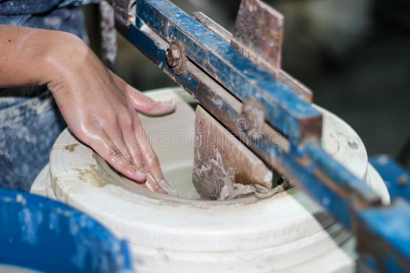 Hands of a potter, creating an bowl using a terraja. Pottery polishing process with 2 hands in the final step. Before entering the kiln royalty free stock photos