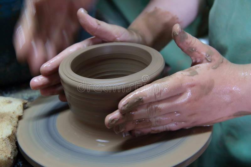 Hands of a potter, creating an earthen jar on pottery wheel. stock photos