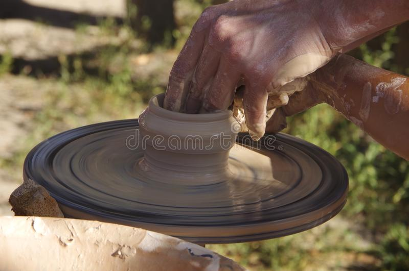 Potter`s wheel with clay. Hands potters make pottery on a potter`s wheel royalty free stock images