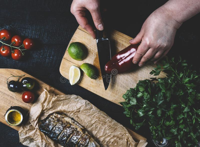 Hands in the process of cooking fish, pepper, parsley, tomato, lime on a cutting board on a black wooden background top view horiz royalty free stock photo