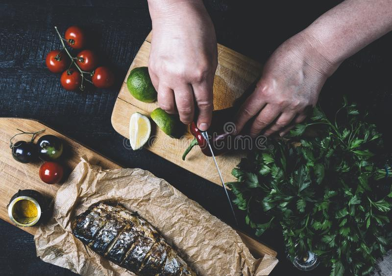 Hands in the process of cooking fish, pepper, parsley, tomato, lime on a cutting board on a black wooden background top view horiz royalty free stock photography