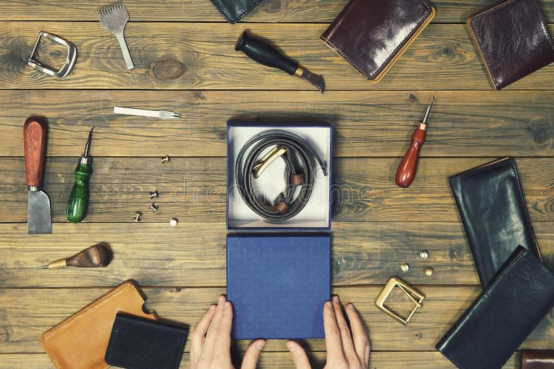 Hands put a new leather wallet in a gift box. conceptual image of a gift to a man. composition of different hand made. Leather man accessories on wooden stock image