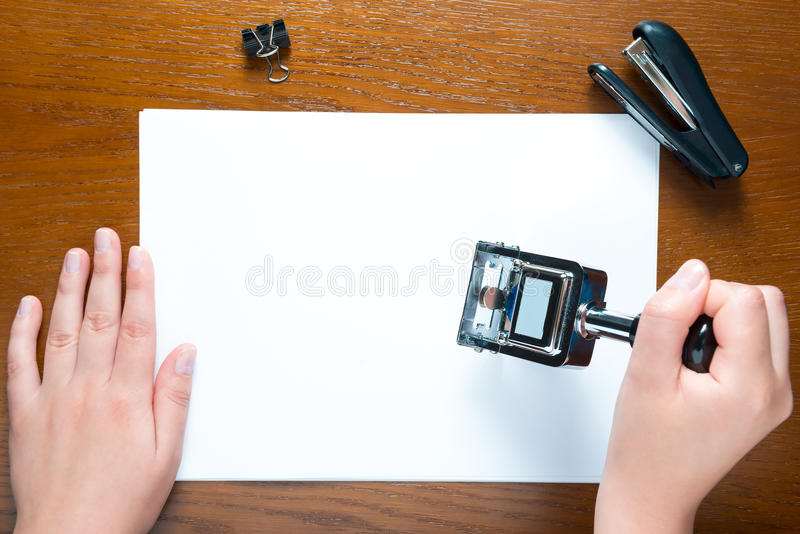 Hands put stamp on the blank sheet of paper royalty free stock image