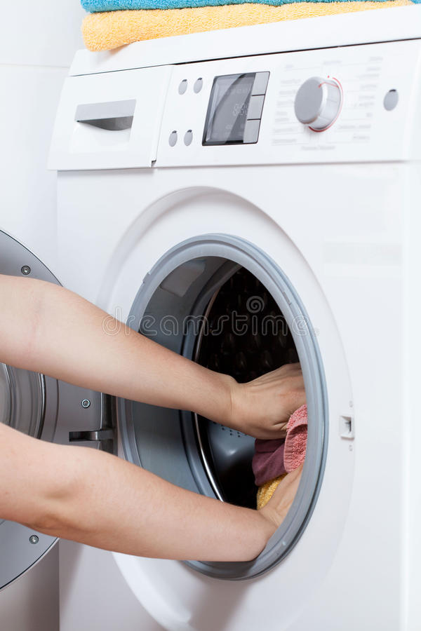 Hands putting laundry into the washing machine drum stock images