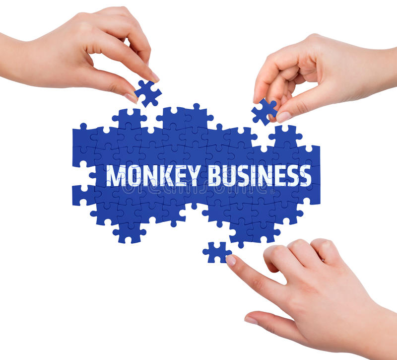 Hands with puzzle making MONKEY BUSINESS word stock image