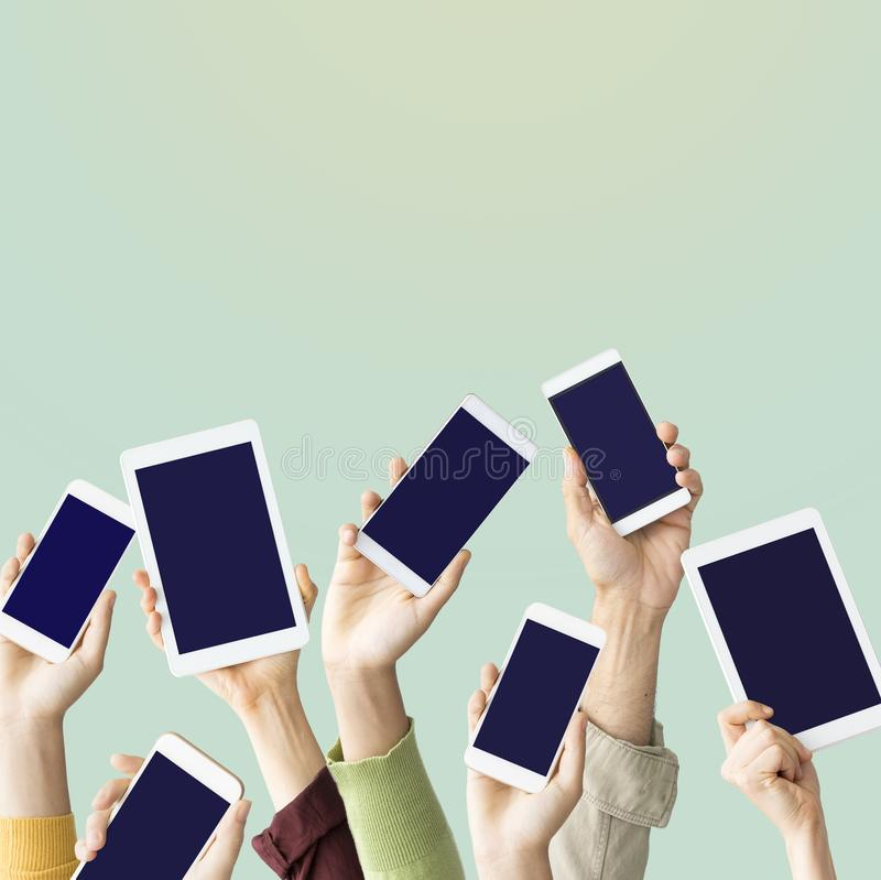 Hands raised holding mobile devices. Hands raised holding mobile  devices royalty free stock images