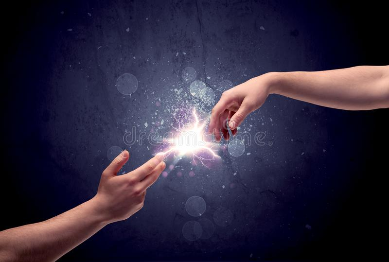 Hands reaching to light a spark stock image