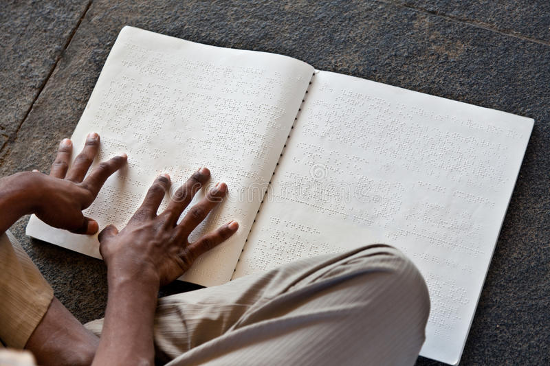 Read Braille. Hands reading a book written in Braille language for the blind stock image