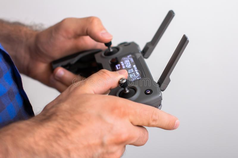 Hands with remote controller of drone outside. Man using RC for flying by drone royalty free stock images