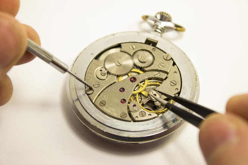 Hands repair an old watch royalty free stock image
