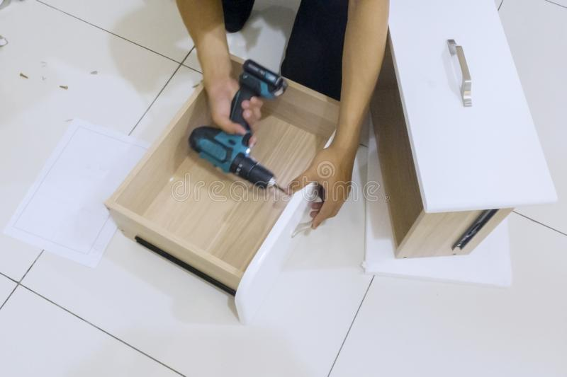 Hands of repairman assembles a drawer with a drill royalty free stock photos