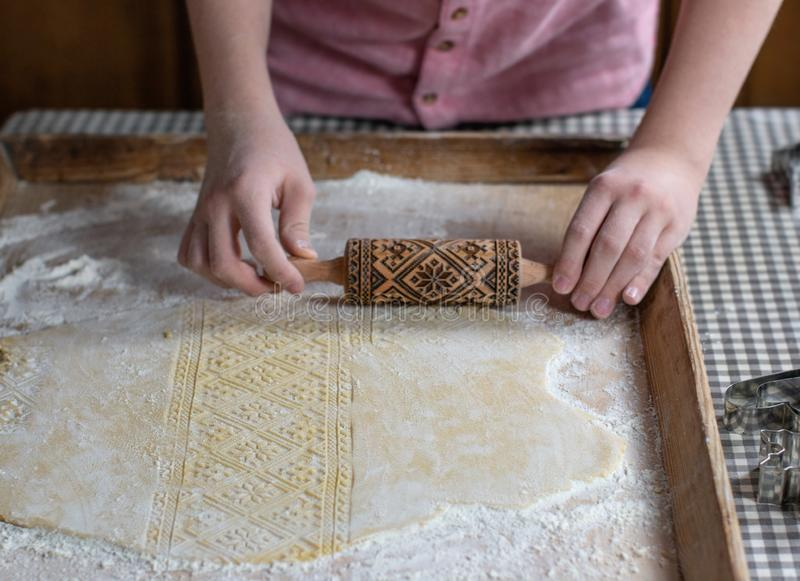 Hands rolling dough with an embossing rolling pin, on a wooden background royalty free stock image