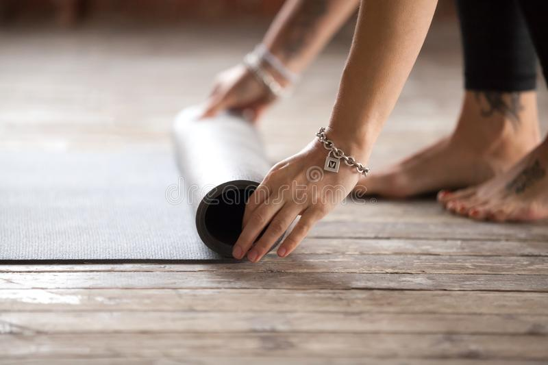 Hands rolling fitness mat. Concept of healthy life stock image