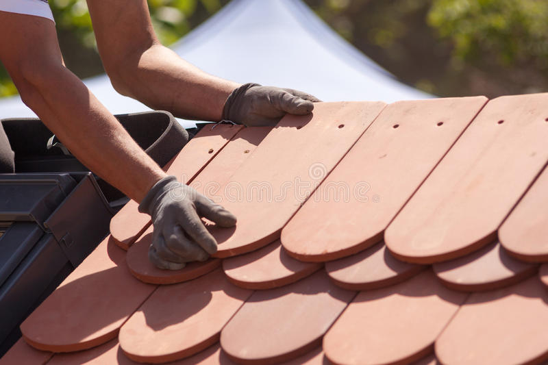 Hands of roofer laying tile on the roof. Installing natural red tile stock images